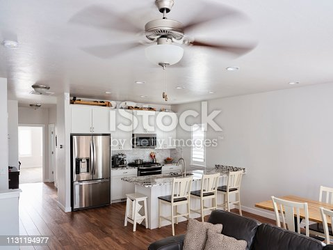 The interior of a modern 'open concept' American residential home with the kitchen, dining area, and family room in a large open space.