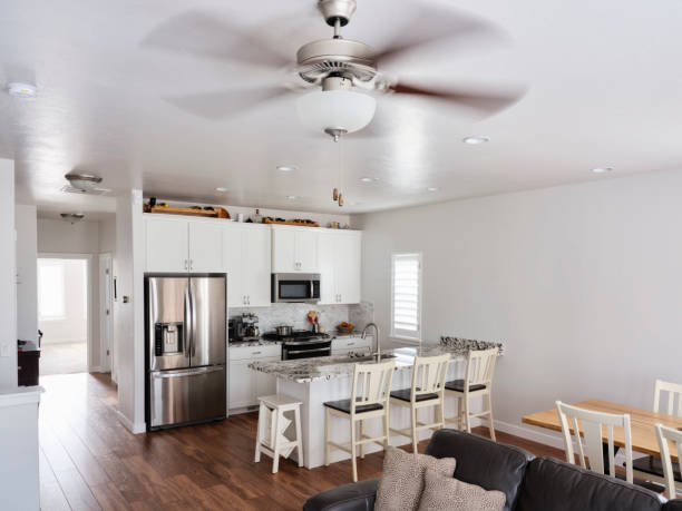 Modern Open Concept Home Interior The interior of a modern 'open concept' American residential home with the kitchen, dining area, and family room in a large open space. ceiling fan stock pictures, royalty-free photos & images