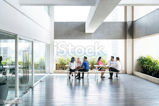 Group of men and women sitting in sparse meeting space with natural light on picnic benches