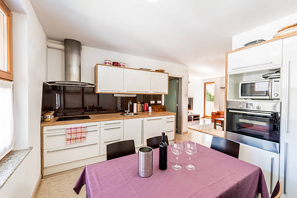 modern open space kitchen with view of living room. - küche deko lila stock-fotos und bilder