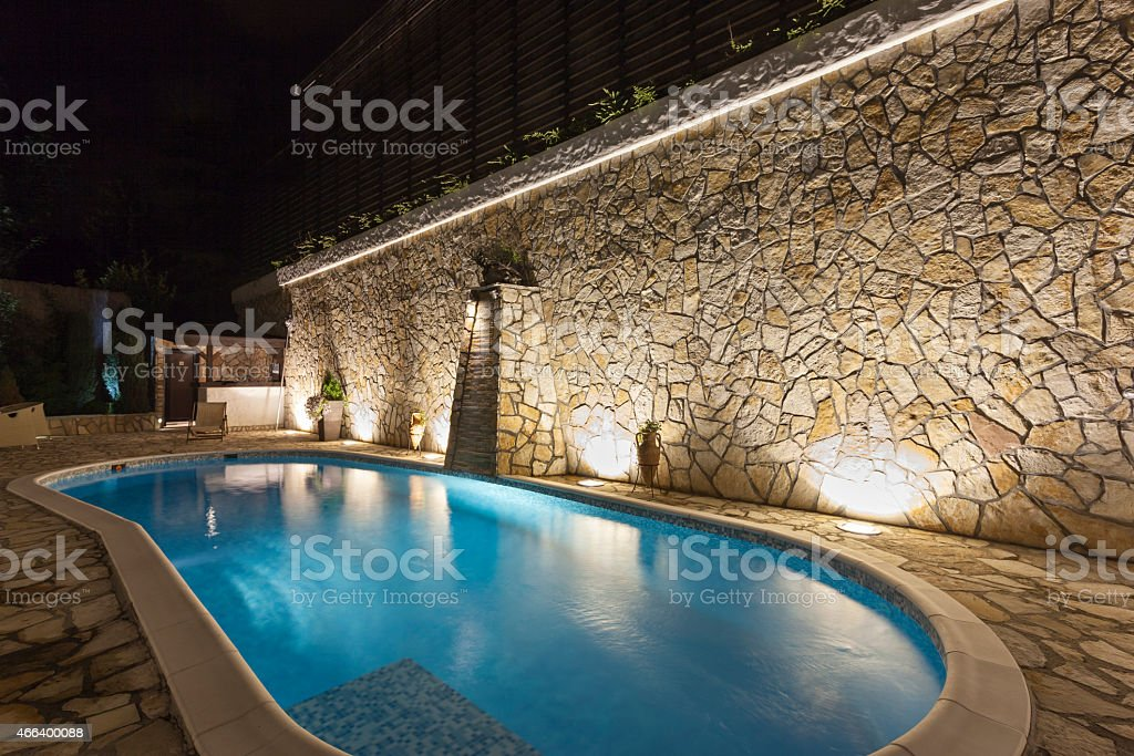 Modern outdoor private swimming pool at night stock photo