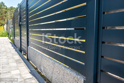 istock Modern panel fencing in anthracite color, visible spans and a wicket, forest in the background. 1270018736