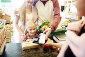 Modern family making contactless payment at supermarket cash-register