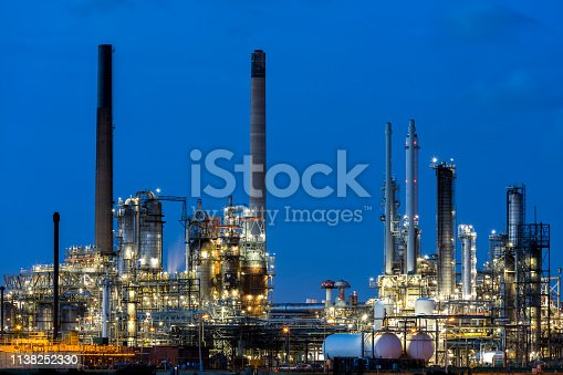 Modern petrochemical plant illuminated at dusk, Netherlands, Benelux, Europe.