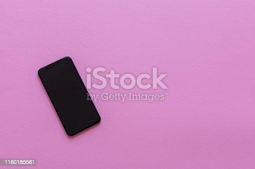 istock Modern phone on pink background 1160185561