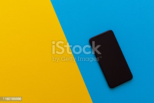 istock Modern phone on yellow and blue background 1160185566