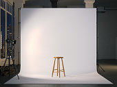 istock Modern photostudio with blank screen and wooden chair. 3d rendering 909546146