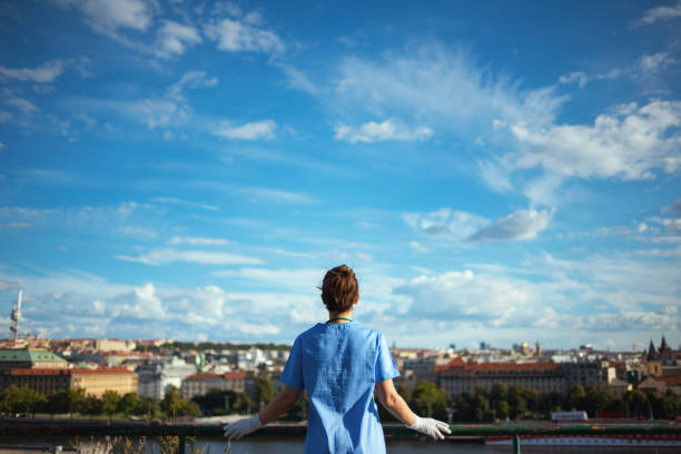 modern physician woman in scrubs outdoors in city against sky stock photo