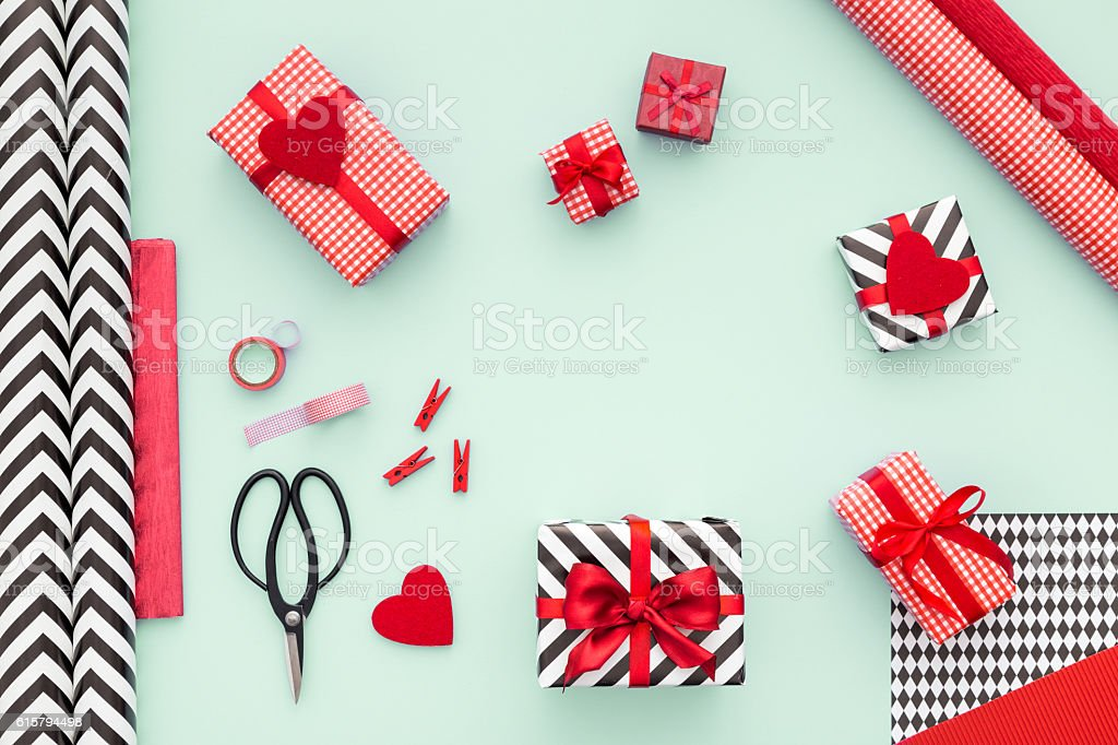 Modern presents boxes laid on mint background. Flat lay. Gift boxes wrapped in red checked paper and the contents of a workspace composed. Different objects on a mint color table. Flat lay.Christmas (xmas) or New year gift packing. Holiday decor concept. Above Stock Photo
