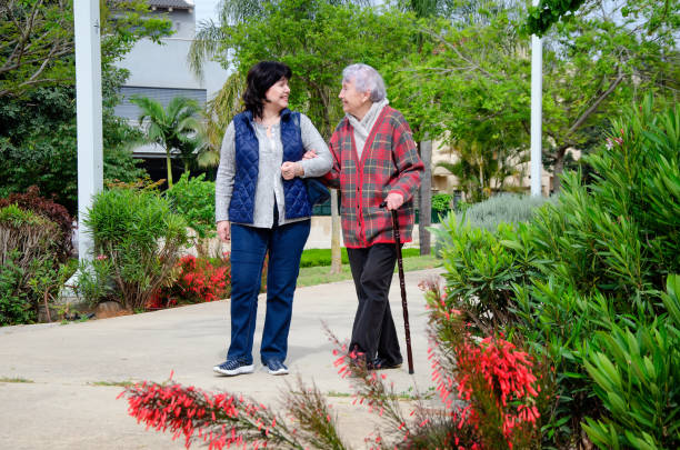 Modern psychotherapist walking with an elderly patient in a city park stock photo