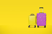 Modern purple yellow suitcases bag on yellow background. luggage set for copy space. minimal concept travel.