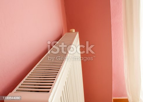 istock Modern radiator on color wall indoors. Central heating system 1133544092