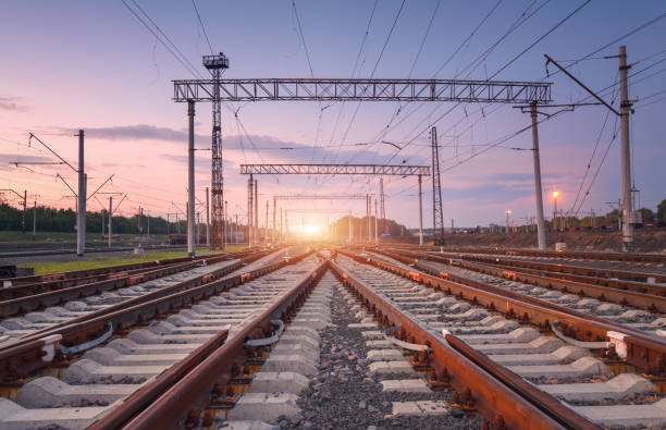 modern railway station at night in europe. industrial landscape with railroad junction, purple sky and sunset. railway platform in twilight. railway background. heavy industry. freight transportation - rail stock photos and pictures