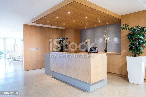 Interior of reception. Lights are illuminated above counter. Empty modern office.