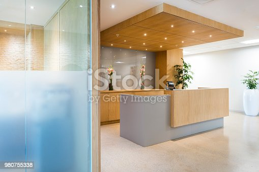 Interior of reception area. Lights are illuminated above counter. Empty modern office or hotel reception.