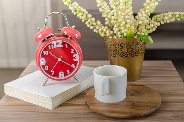modern red alarm clock on book with cup stock photo