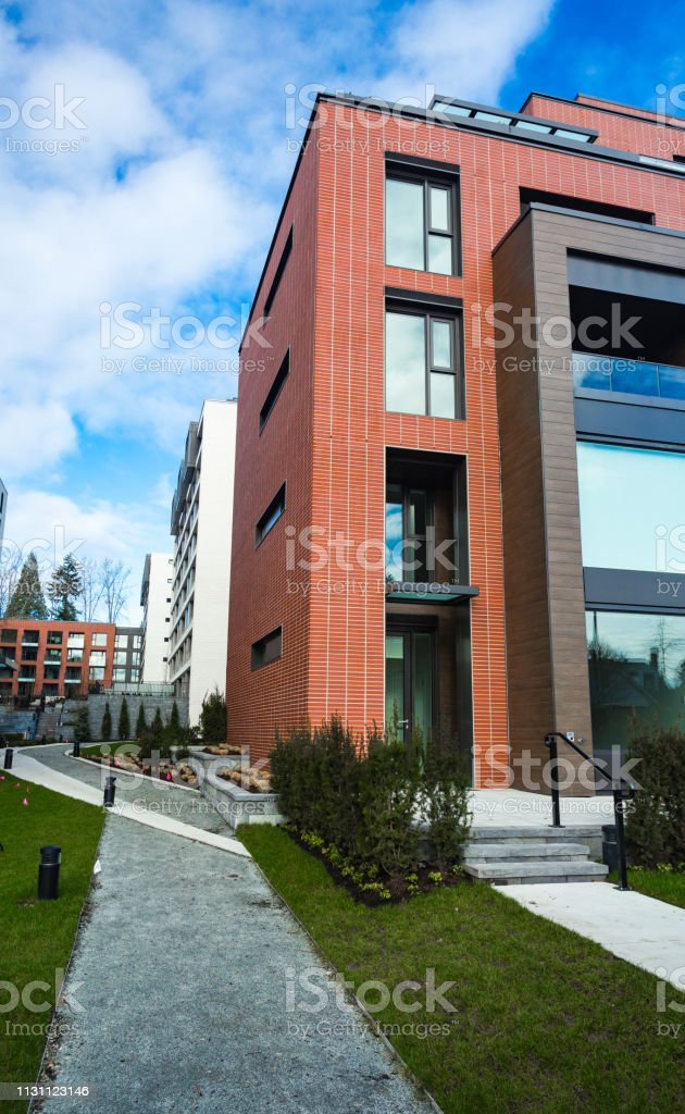 Modern Red Brick Apartment Complex with solid rock fence wall. Home...