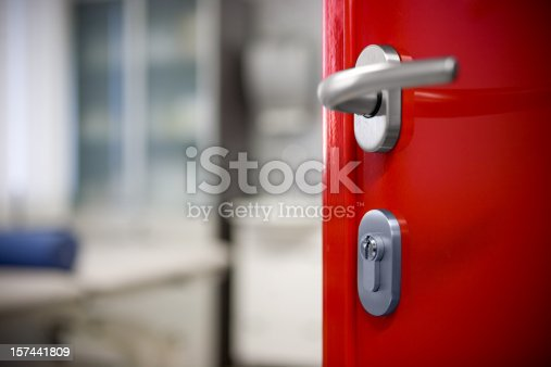 Modern red door with silver metal handle, office ambience.