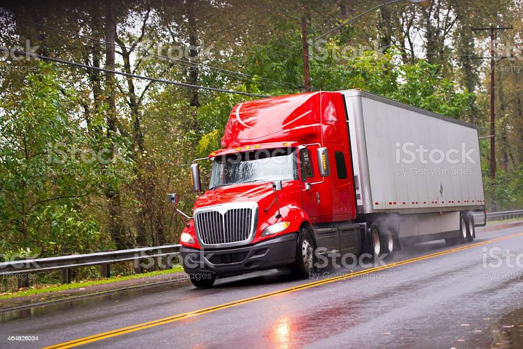 Modern red glossy in rain semi truck trailer raining road stock photo