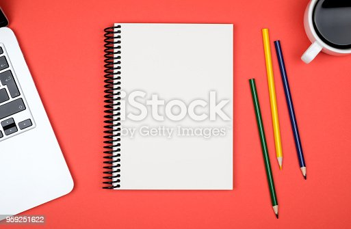 istock Modern red office desk table with laptop and blank notebook page for input the text. Top view, flat lay 959251622