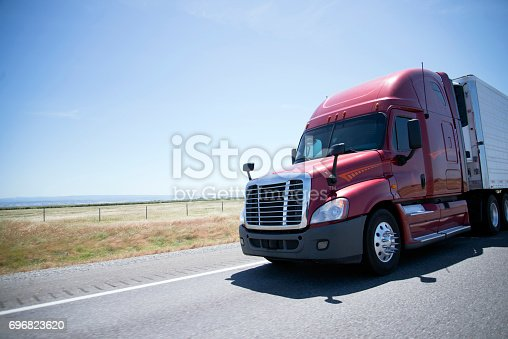 A large, powerful modern semi truck with a reefer unit and refrigerated trailer carries perishable cargoes that require storage at low temperatures along the direct roads of sunny California