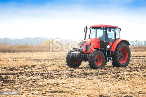 Modern red tractor in the field on a bright sunny day