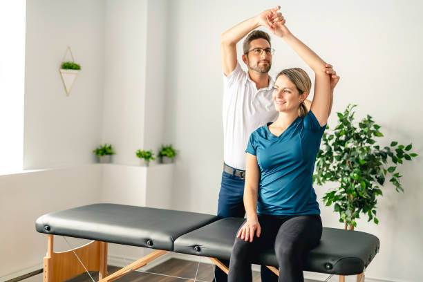 a modern rehabilitation physiotherapy man at work with woman client - sports medicine stock pictures, royalty-free photos & images