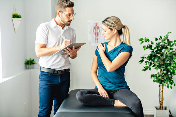 A Modern rehabilitation physiotherapy man at work with woman client talk about shoulder problem stock photo