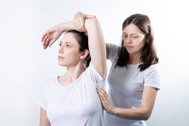 a modern rehabilitation physiotherapy woman at work with woman client - physical therapy стоковые фото и изображения