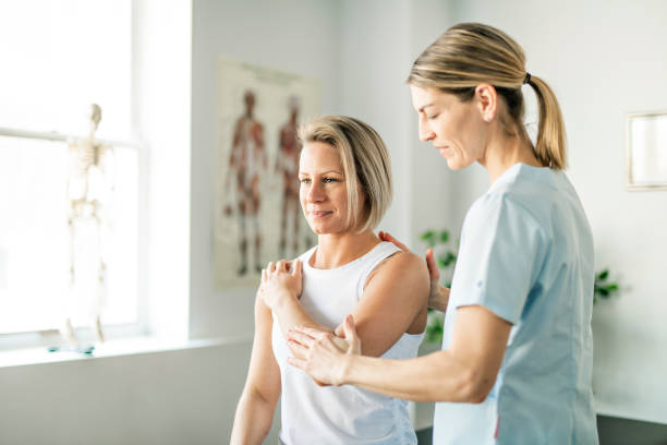 a modern rehabilitation physiotherapy worker with woman client - physical therapy стоковые фото и изображения
