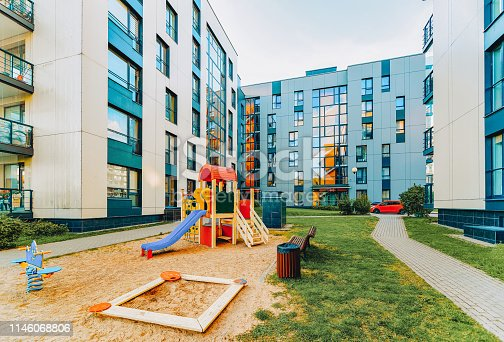 1165384568 istock photo Modern residential apartment flat house building and children playground 1146068806