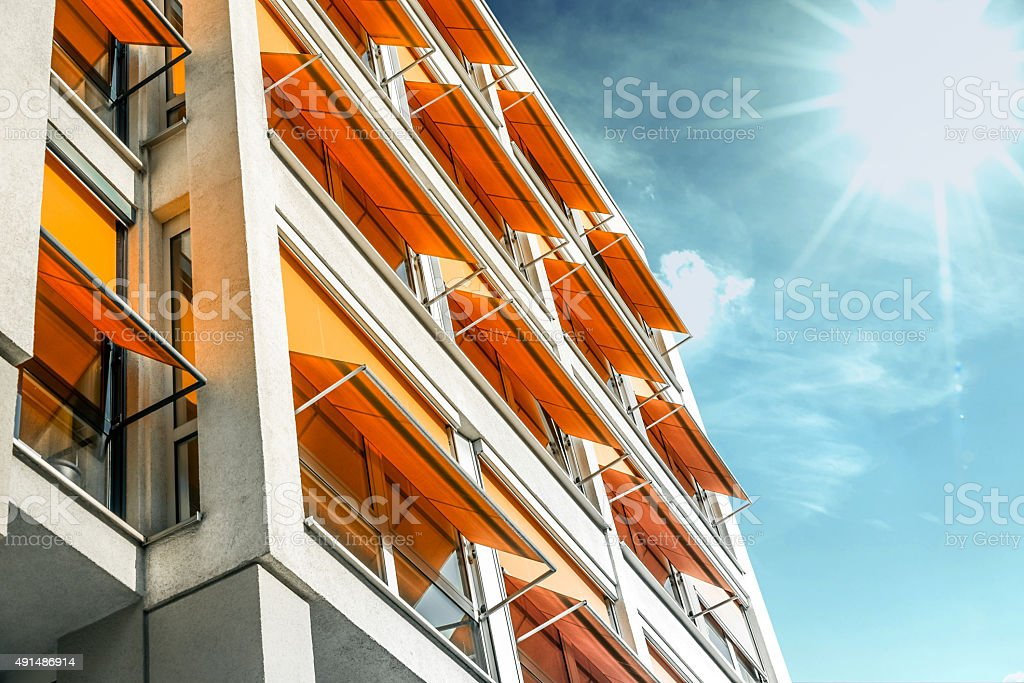modern residential house with orange awnings in sunny Berlin stock photo