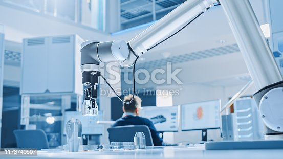 968289374istockphoto Modern Robot Arm Picks up, Lifts and Moves Metal Component as Programmed. In the Background Industrial Robotics Engineers Working on Software, Programming and Machine Learning in Engineering Facility 1173740507