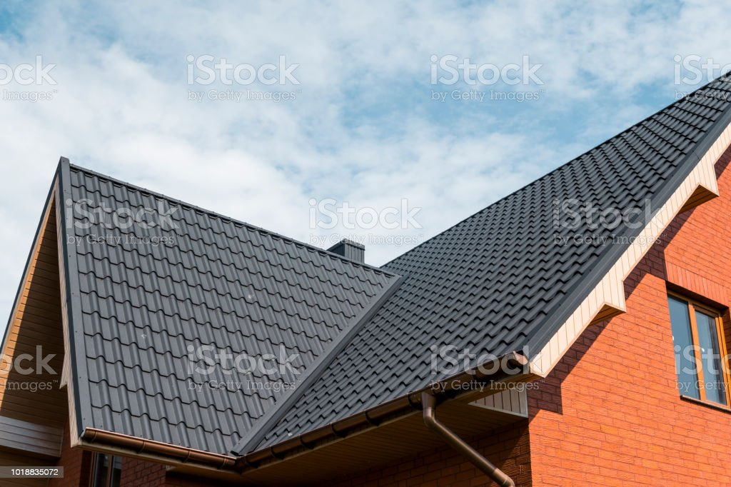 Modern roof covered with tile effect PVC coated brown metal roof sheets. royalty-free stock photo