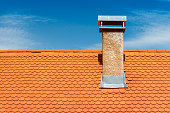 Modern roof with chimney. Orange ceramic tile, shingle. Blue sky on the background.