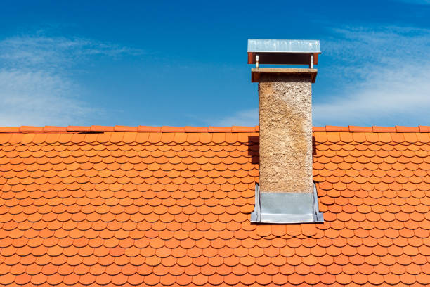 Modern roof with chimney. Orange ceramic tile, shingle. Blue sky on the background stock photo