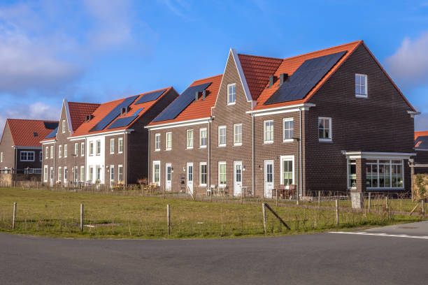 Modern row houses with red roof tiles on sunny day stock photo