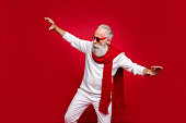 istock Modern santa character aged man moving like star at party wear sun specs knitted clothes isolated red background 1169342698