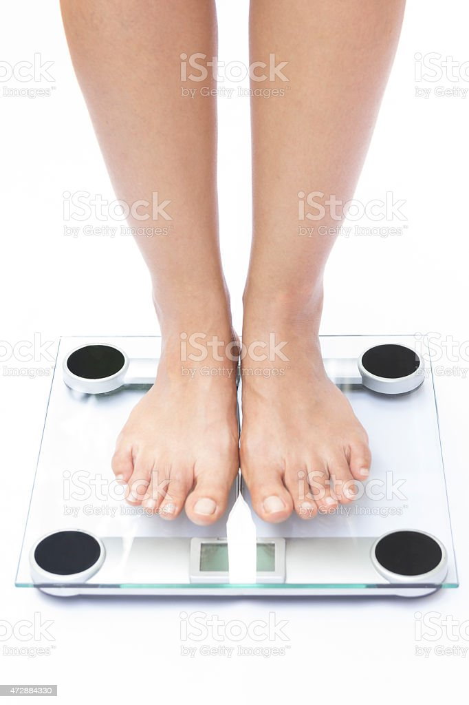 A modern scale with two feet standing on it stock photo
