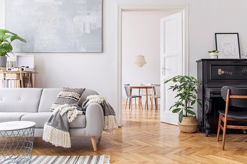 Modern scandianvian decor of living room with design sofa with elegant blanket, coffee table and bookstand on the white wall. Brown wooden parquet. Concept of minimalistic interior with piano. Mock up