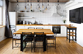 istock Modern scandinavian an eat-in kitchen interior design with big wooden table and chairs against light wood floor, bright white walls and furnitures with TV, appliances and hanging light bulbs 1221223087