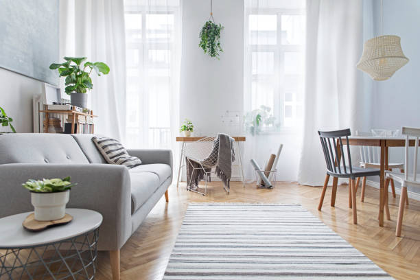 Modern scandinavian living room with design furniture, family table, plants, bamboo bookstand and wooden desk. Brown wooden parquet. Abstract painting on the white wall. Nice apartment. Modern scandianvian decor of living room. Concept of minimalistic interior. northern europe stock pictures, royalty-free photos & images