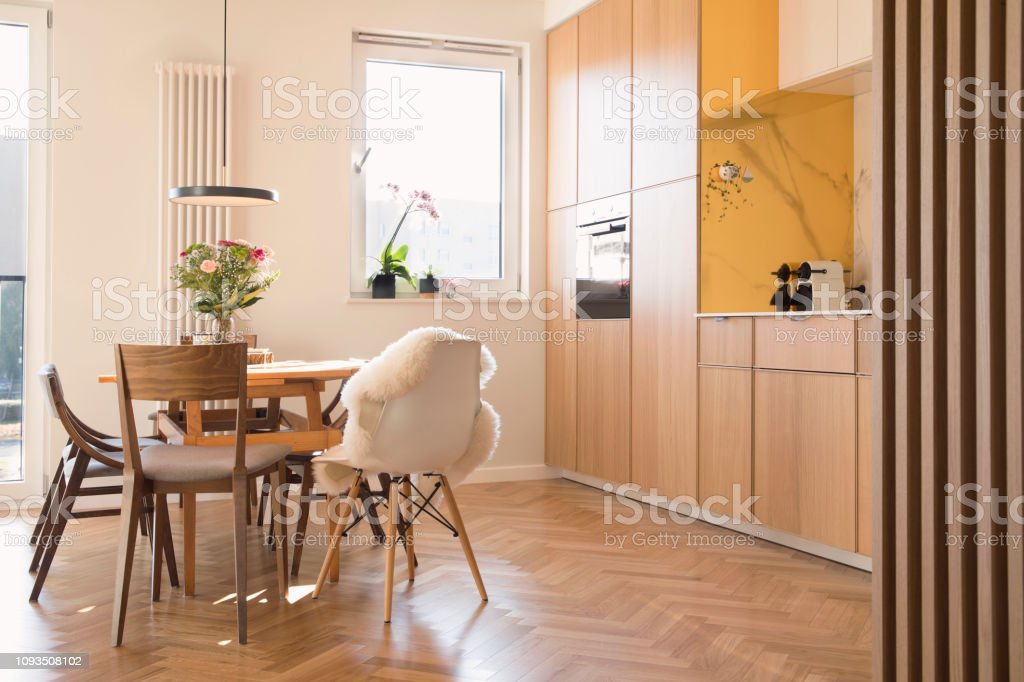 Modern Scandinavian Open Space Interior Of Kitchen And Dining Room With Design Furniture Black Fridge Marble Walls And Brown Wooden Parquet Wooden And Marble Walls Elegant Accessories Stock Photo Download Image