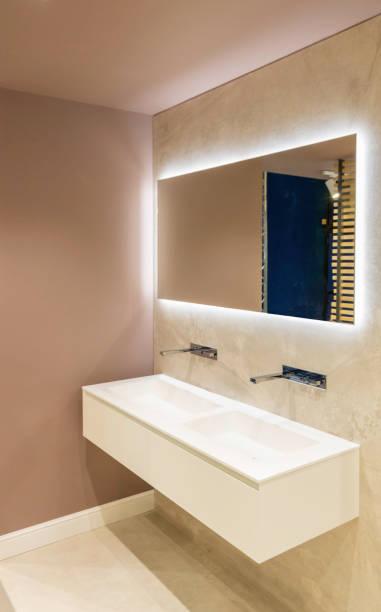 modernes hygge-badezimmer im skandinavischen stil mit einem aufgehängten doppelverschluss-waschbeckenschrank und einem großen spiegel mit retro-beleuchtung - französisches haus dekor stock-fotos und bilder