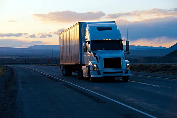 modern semi truck trailer on twilight highway - umzug transport stock-fotos und bilder