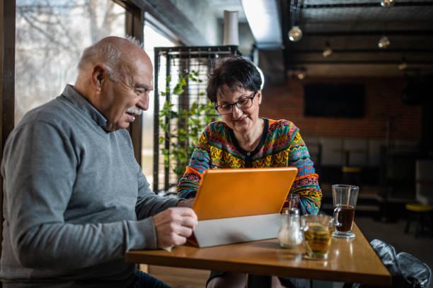 Modern senior couple in cafe stock photo
