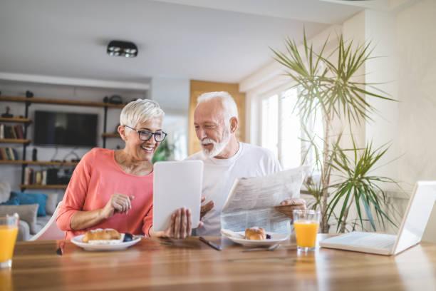 moderna senior par titta på tidningen och en tablett vid frukost - mänsklig bosättning bildbanksfoton och bilder