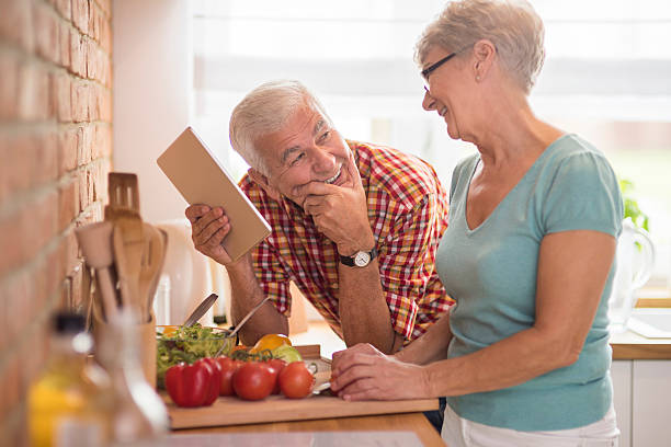 modern senior couple spending time in the kitchen - home cooking stock photos and pictures