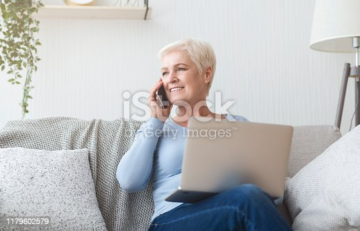 Modern happy senior woman sitting on sofa at home, holding laptop and talking by phone, free space
