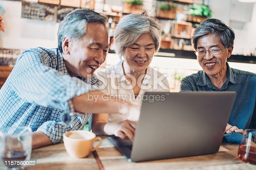 Group of smiling Asian ethnicity people using laptop in cafe